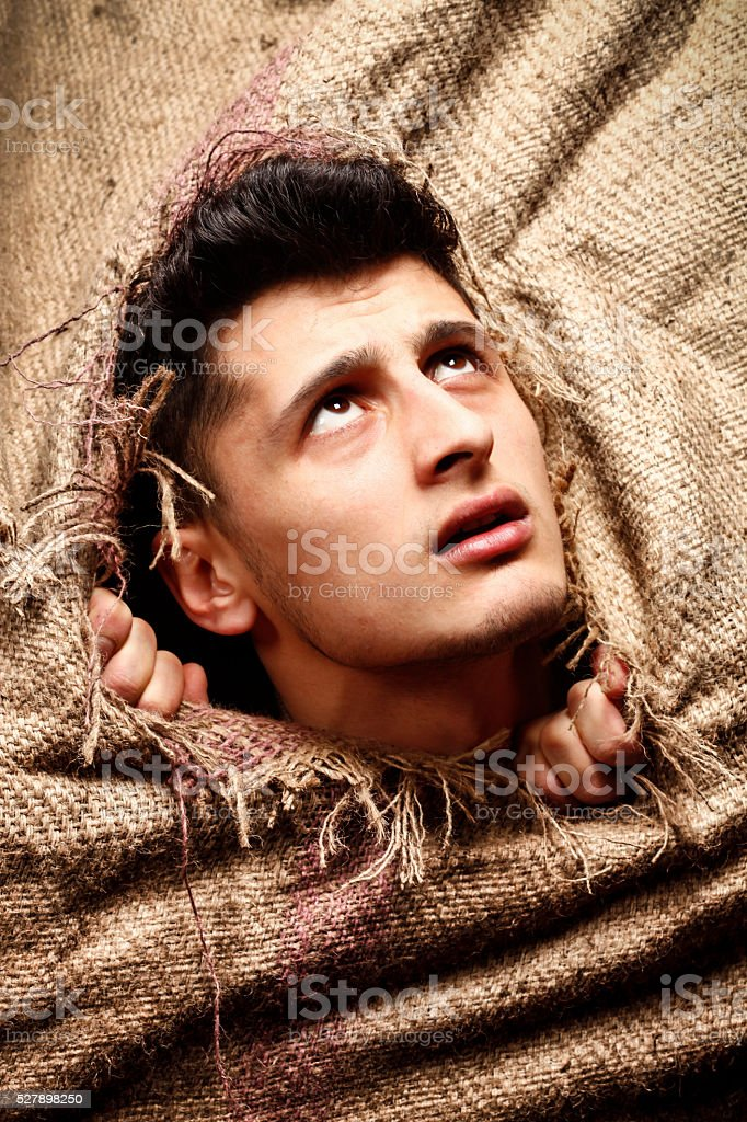 Young man looking through hole stock photo