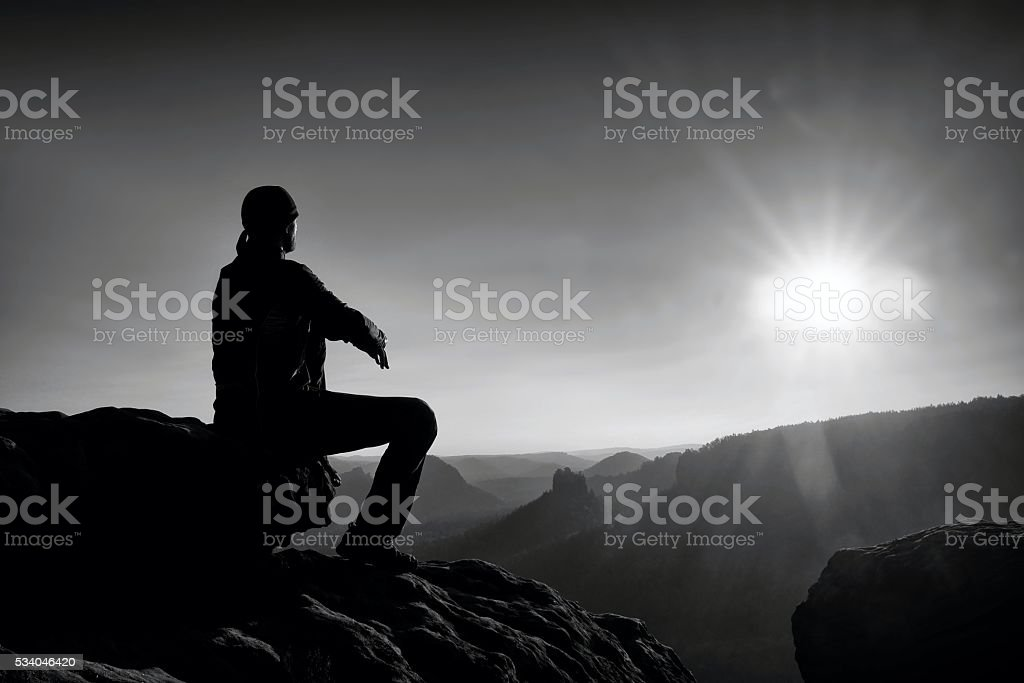 Young man looking to misty valley bellow stock photo
