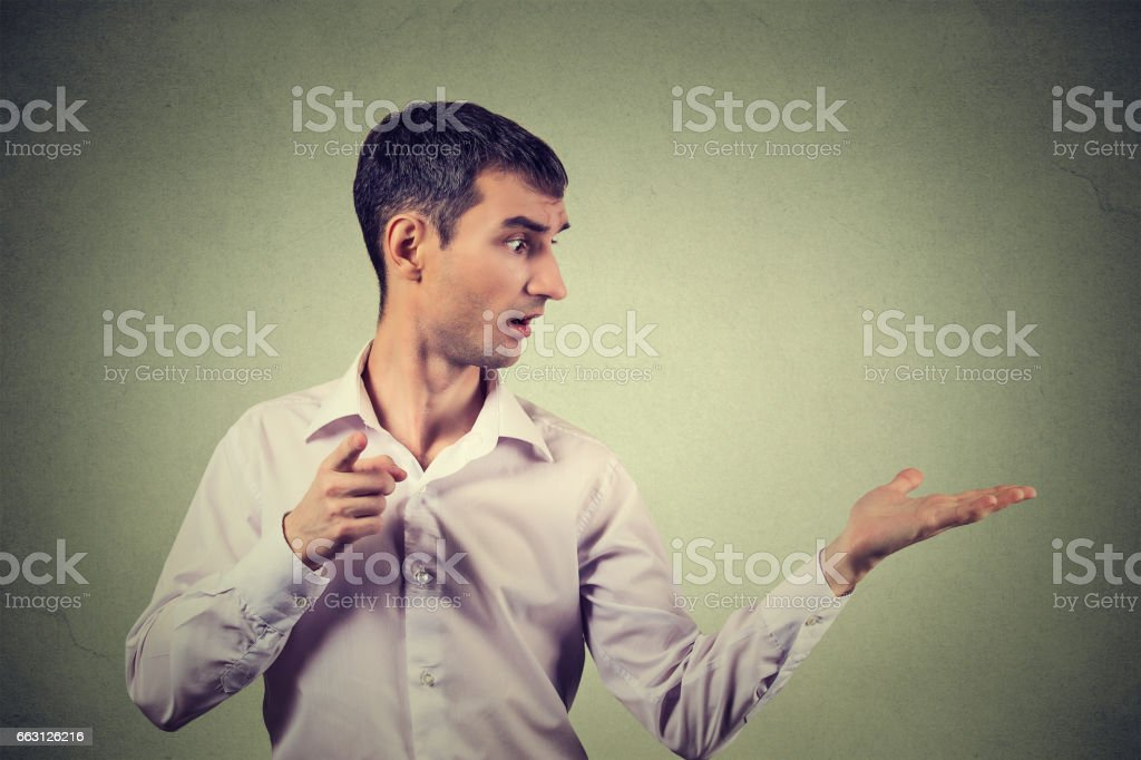 young man looking to side while pointing at your camera stock photo