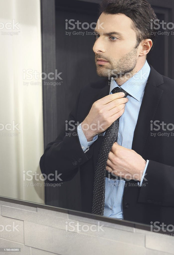 Young man looks at himself in the mirror royalty-free stock photo