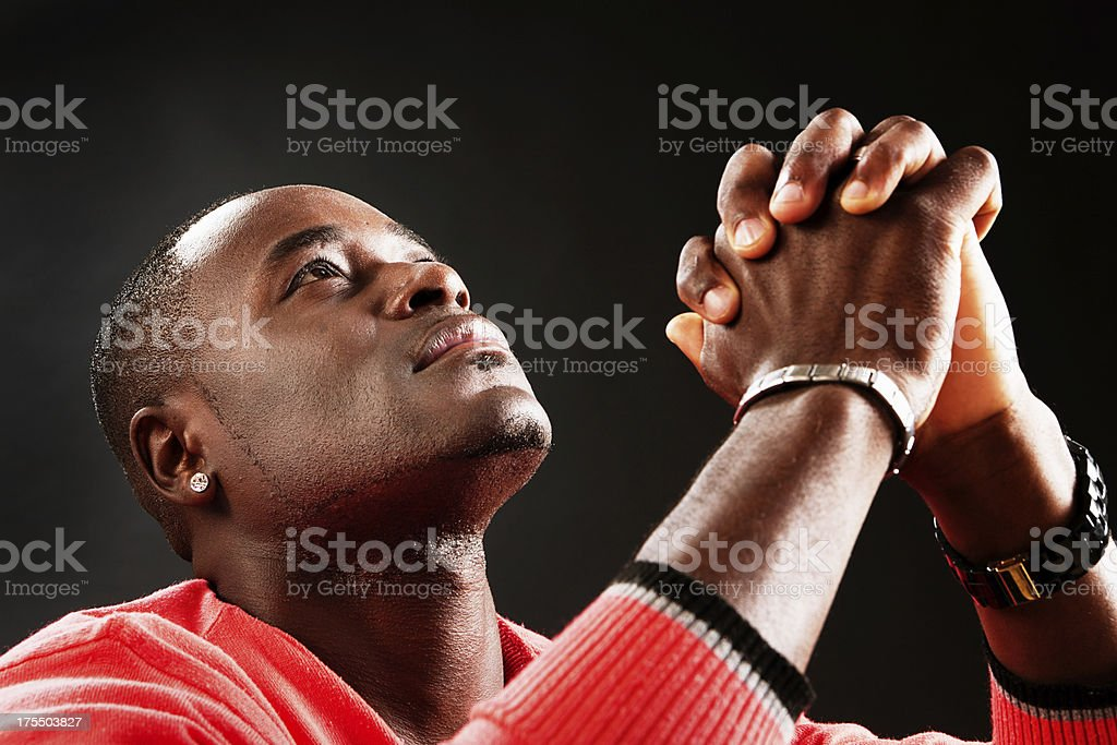 Young man looks up, hands clasped, praying fervently stock photo