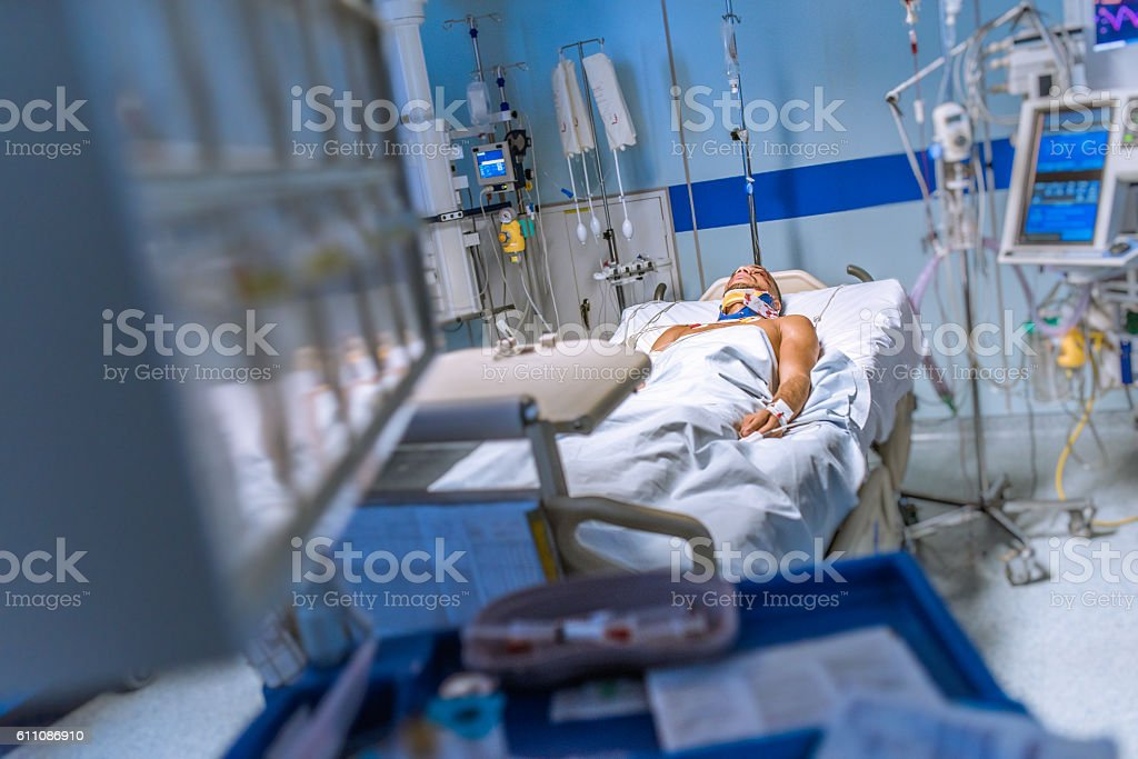 Young man lying in a hospital bed strapped to machines stock photo