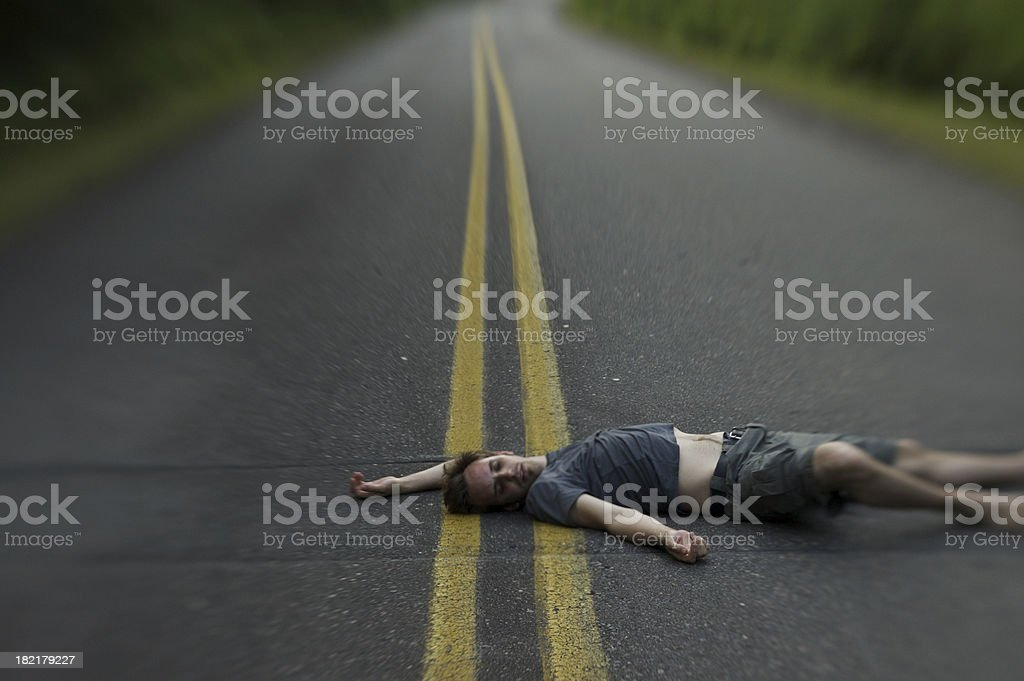 Young Man Lying in the Middle of Road stock photo