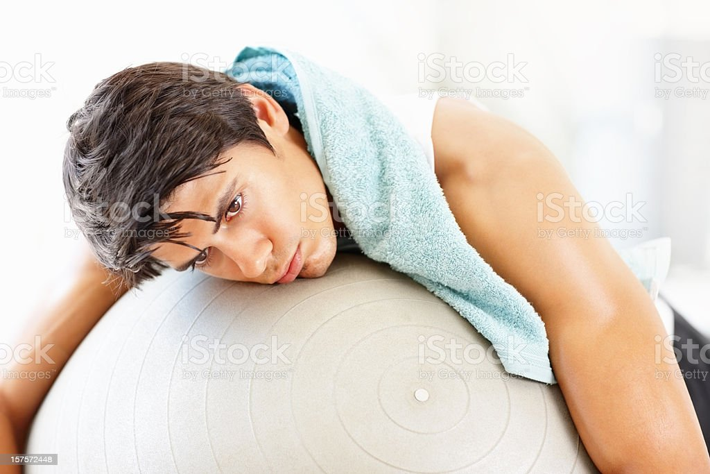 Young man lying on a fitness ball after workout royalty-free stock photo