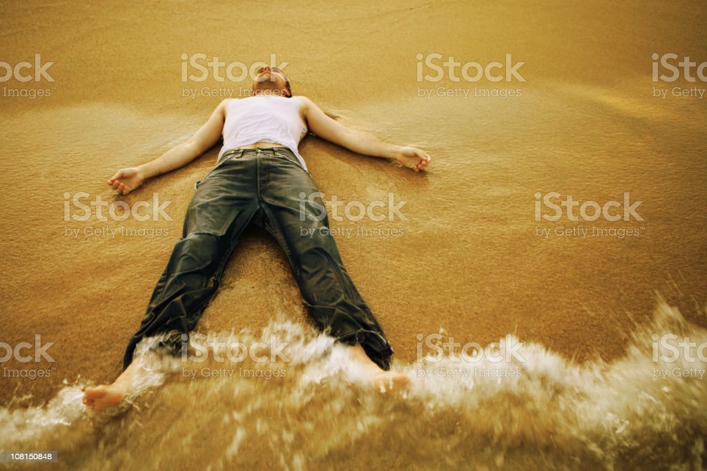 Young Man Lying on Beach and Letting Waves Hit Him stock photo