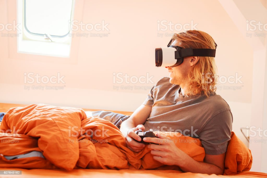 Young man lying on bed, using VR glasses stock photo