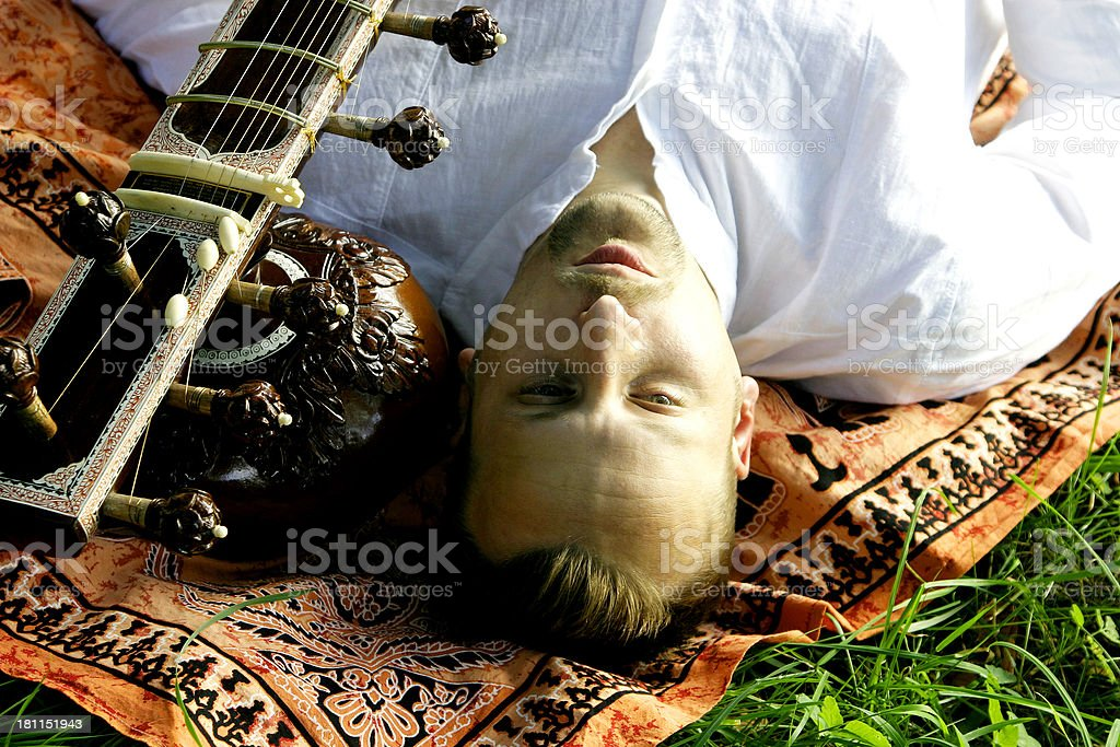 Young Man Lying on Ethnic Scarf Beside Sitar royalty-free stock photo