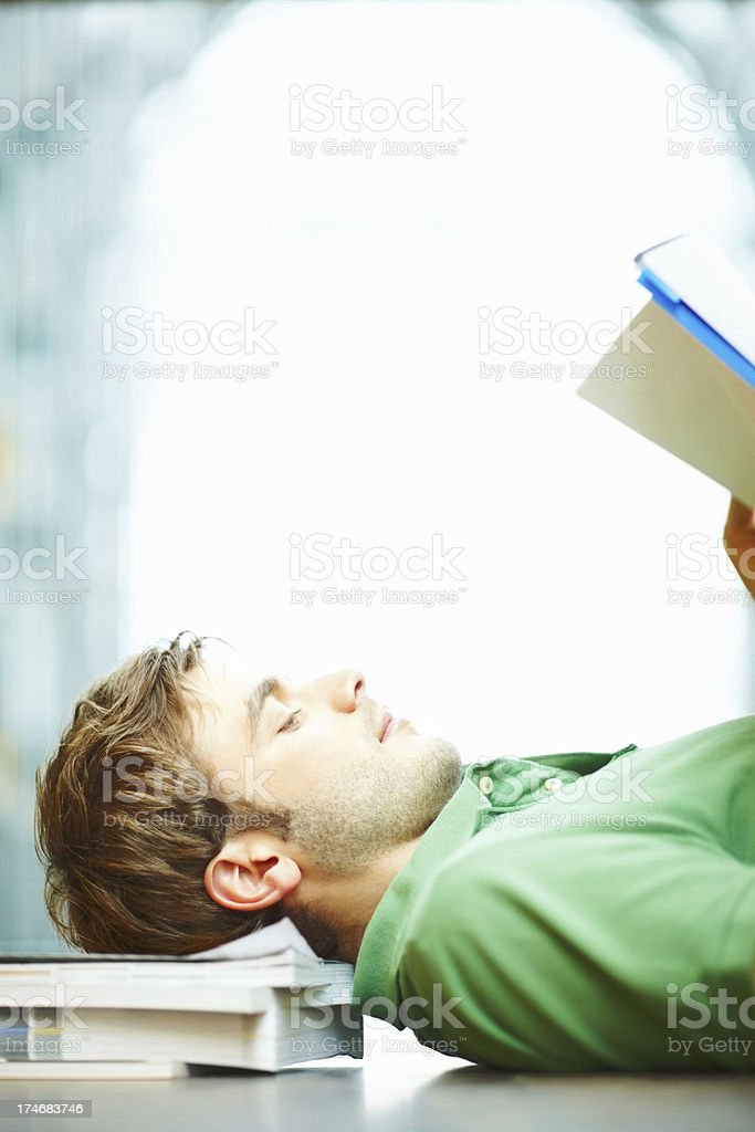Young man lying on the floor and reading a book royalty-free stock photo