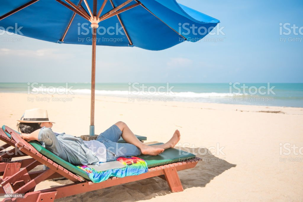 young man lying on wooden beach bench with blue umbrella stock photo