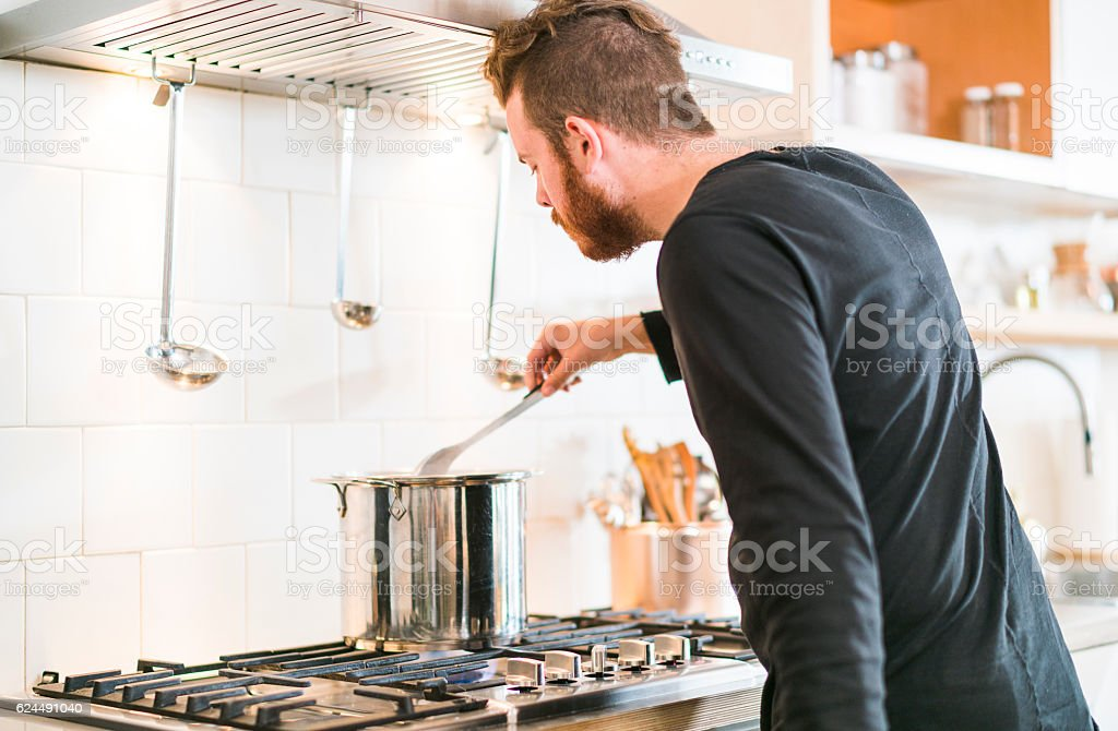 Young man make soup in kitchen stock photo