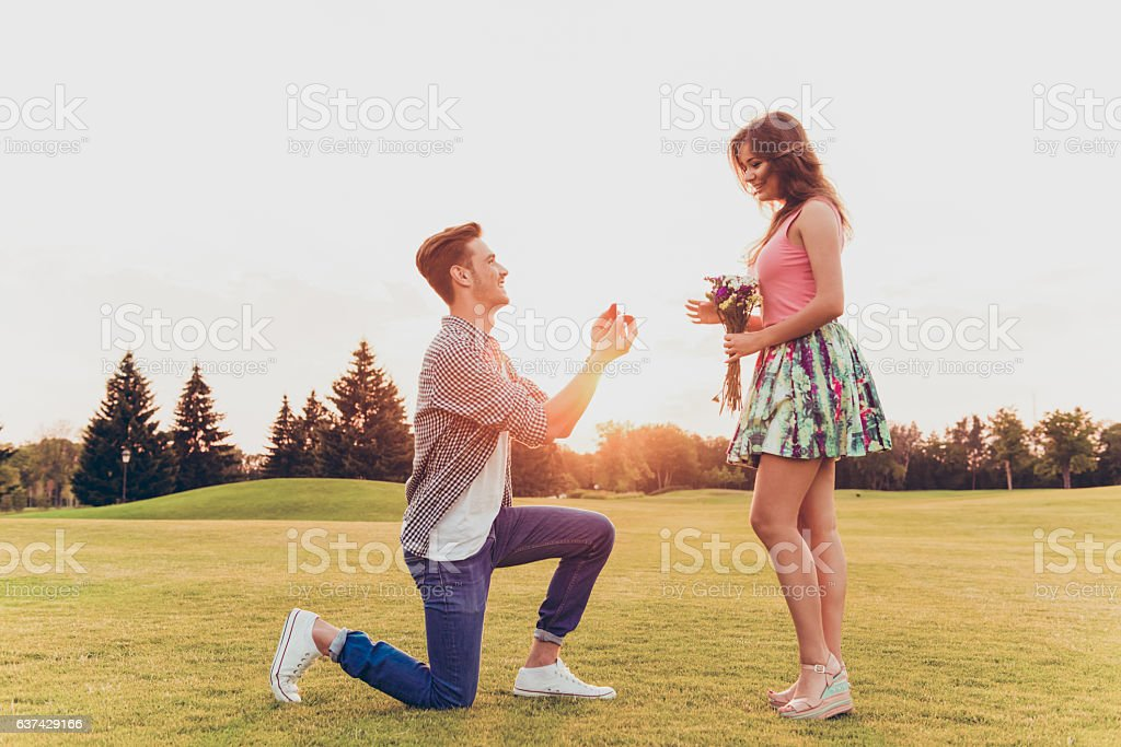 young man makes a proposal of betrothal to his girlfriend stock photo