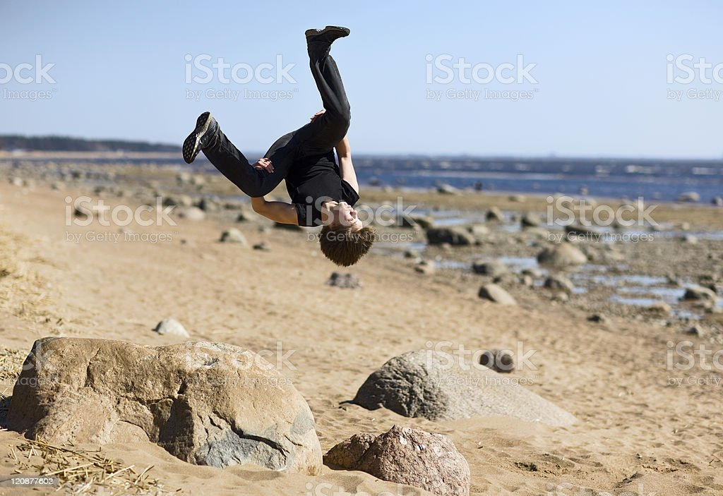 Young man makes extreme jump-overturn over stones. royalty-free stock photo