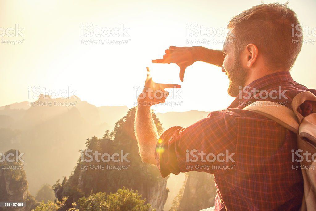 Young man makes natural frame on mountain landscape-concept stock photo
