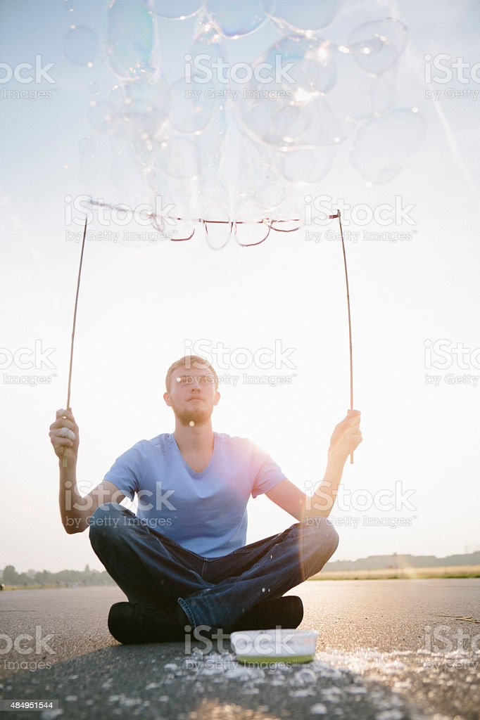 young man makes soap bubbles, sitting on the ground stock photo