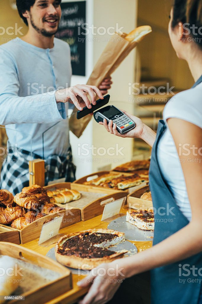 Young man making a contactless payment at a bakery stock photo