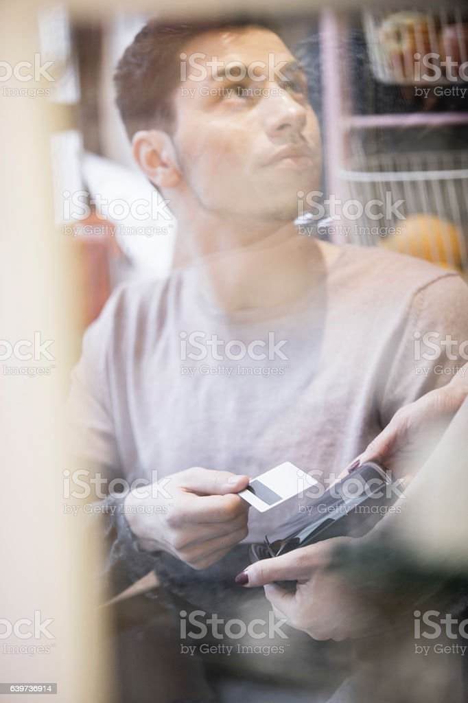 Young man making a payment with pay pass card stock photo
