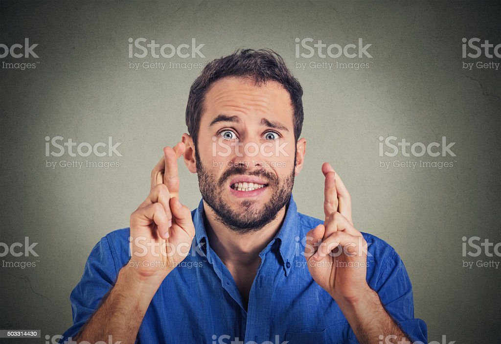 Young man making a wish crossing his fingers stock photo