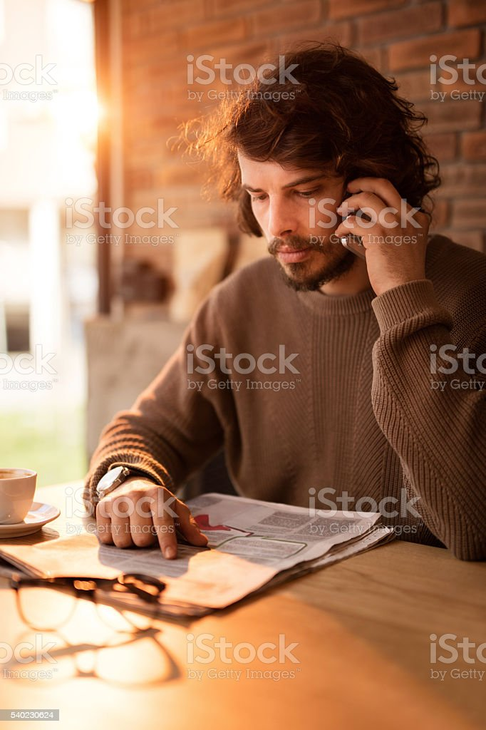 Young man making appointment for job interview over cell phone. stock photo