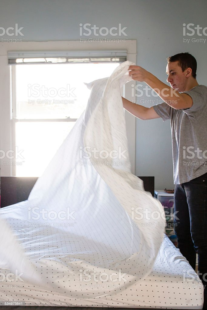 Young Man Making Bed With Clean Sheets stock photo