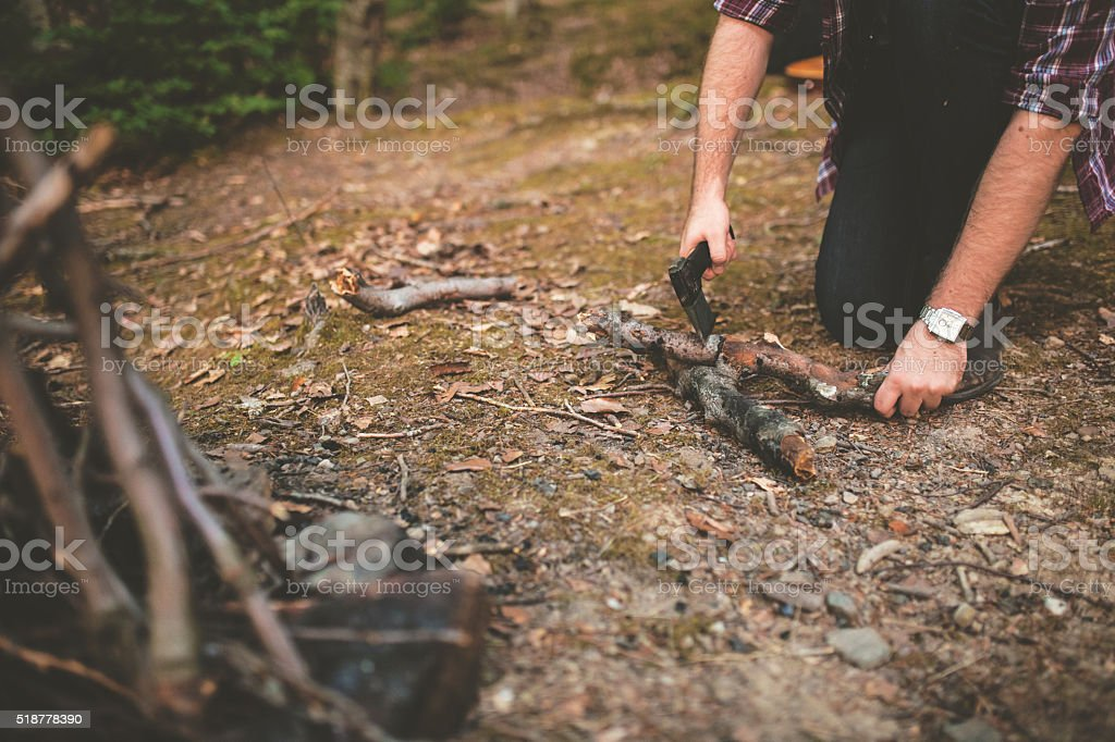 Young man making campfire stock photo