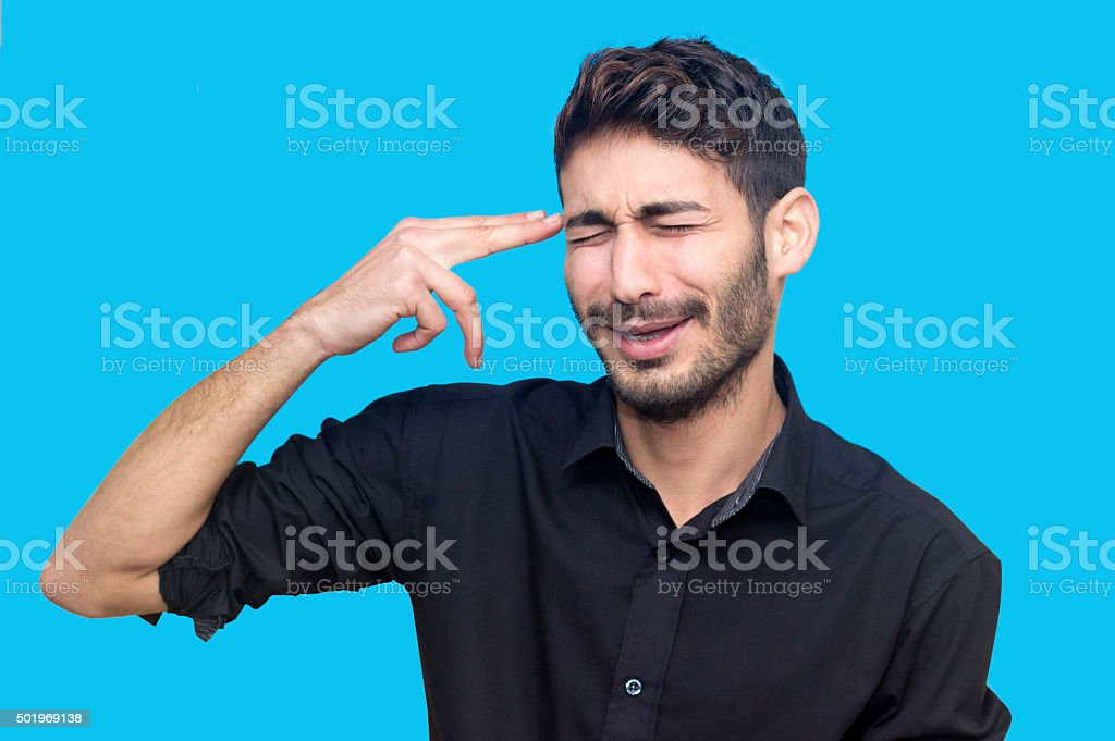 Young man making hand sign gun and holding himself stock photo
