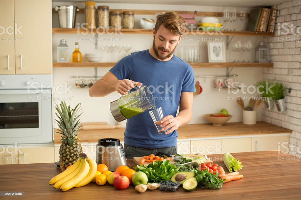 Young man making juice or smoothie in kitchen. stock photo