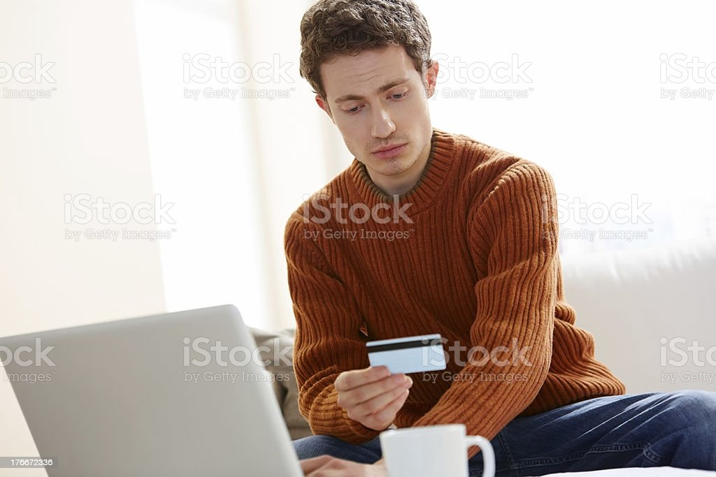 Young man making online payments with credit card royalty-free stock photo