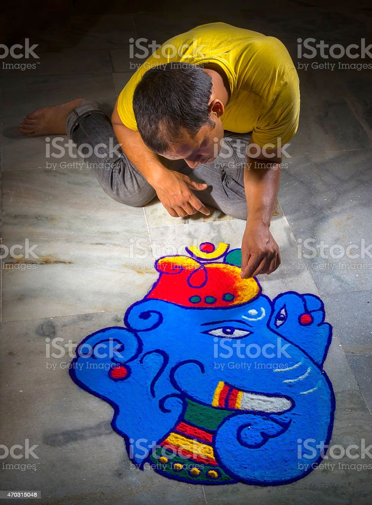 Young man making Rangoli on the occasion of Diwali stock photo