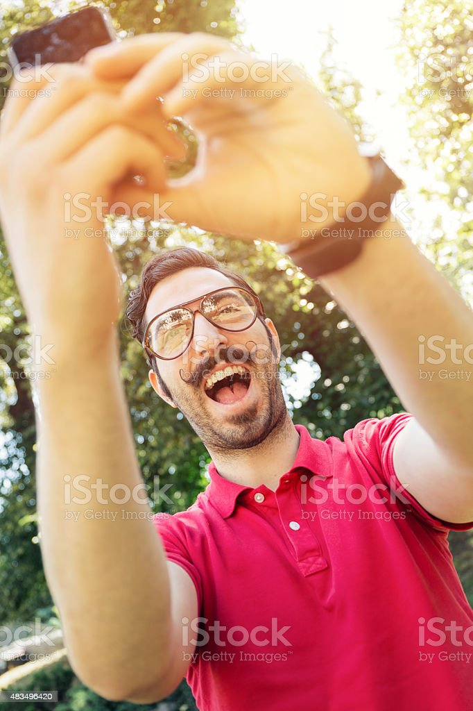 Young man making selfie in the park stock photo