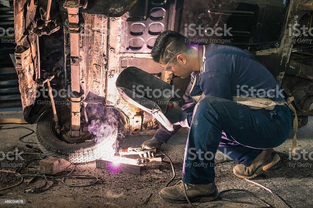 Young man mechanic worker repairing old vintage car body stock photo