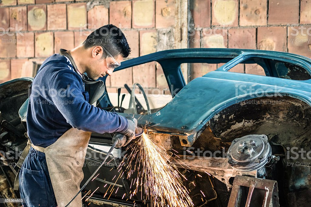 Young man mechanical worker repairing an old vintage car stock photo
