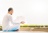 Young man meditating by swimming pool, yoga or relax concept