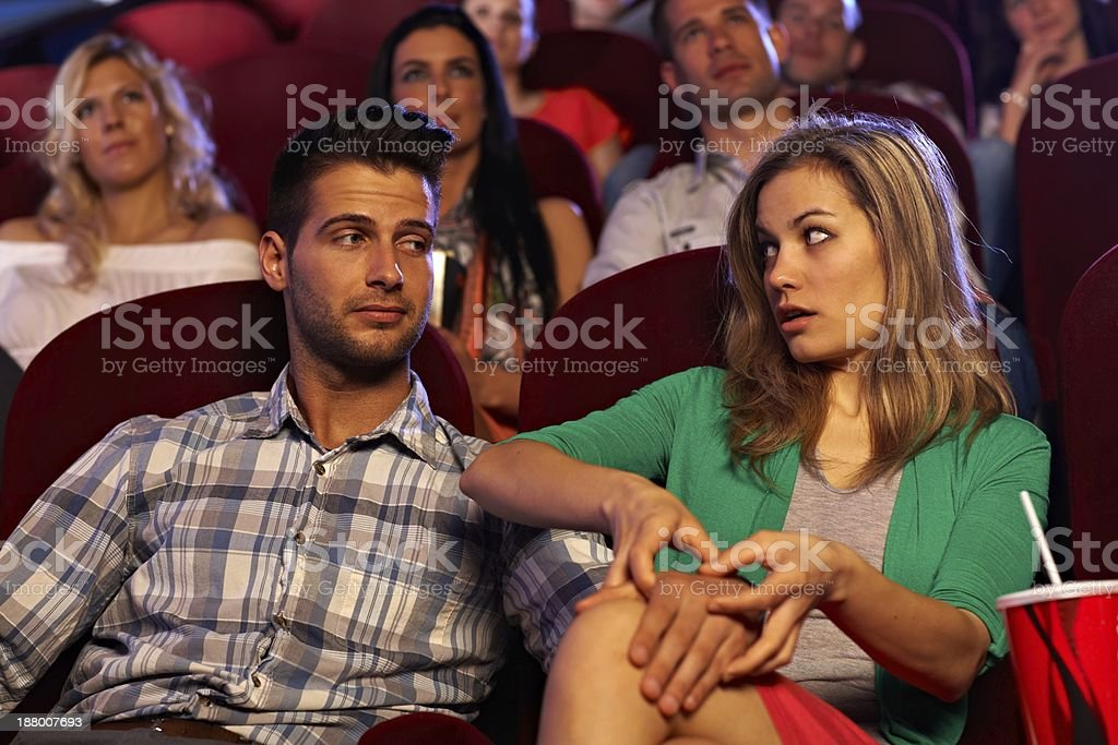 Young man molesting girl in cinema on first date stock photo