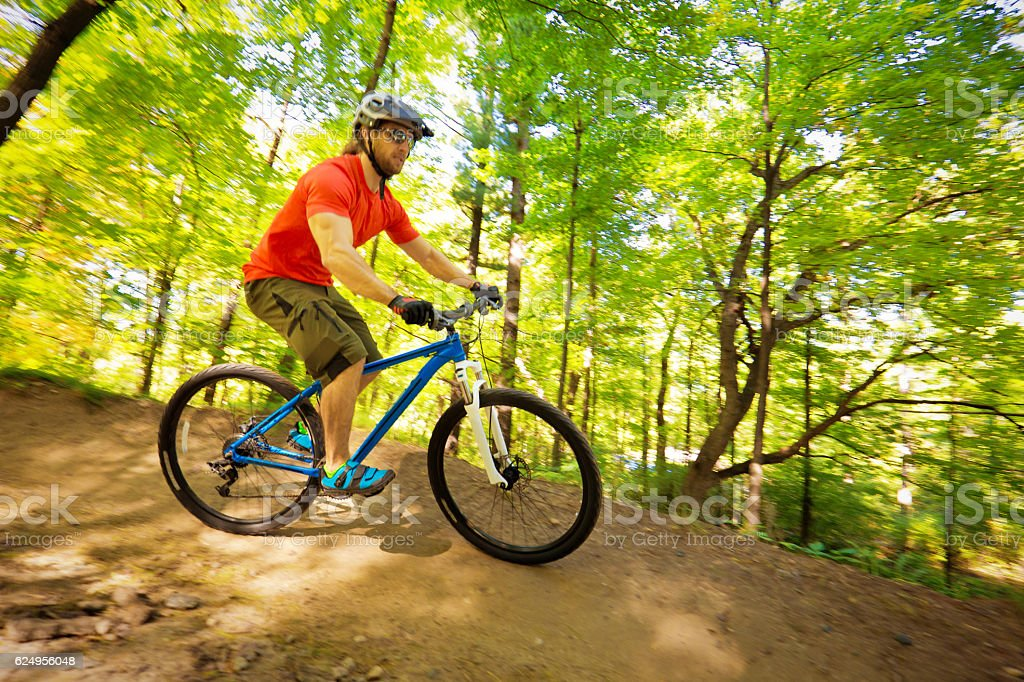 Young Man Mountain Biking in Forest Trail stock photo