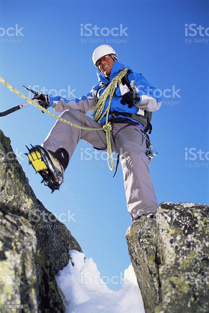 Young man mountain climbing on snowy peak stock photo