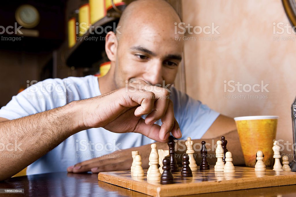 Young Man Moves A Chess Piece stock photo