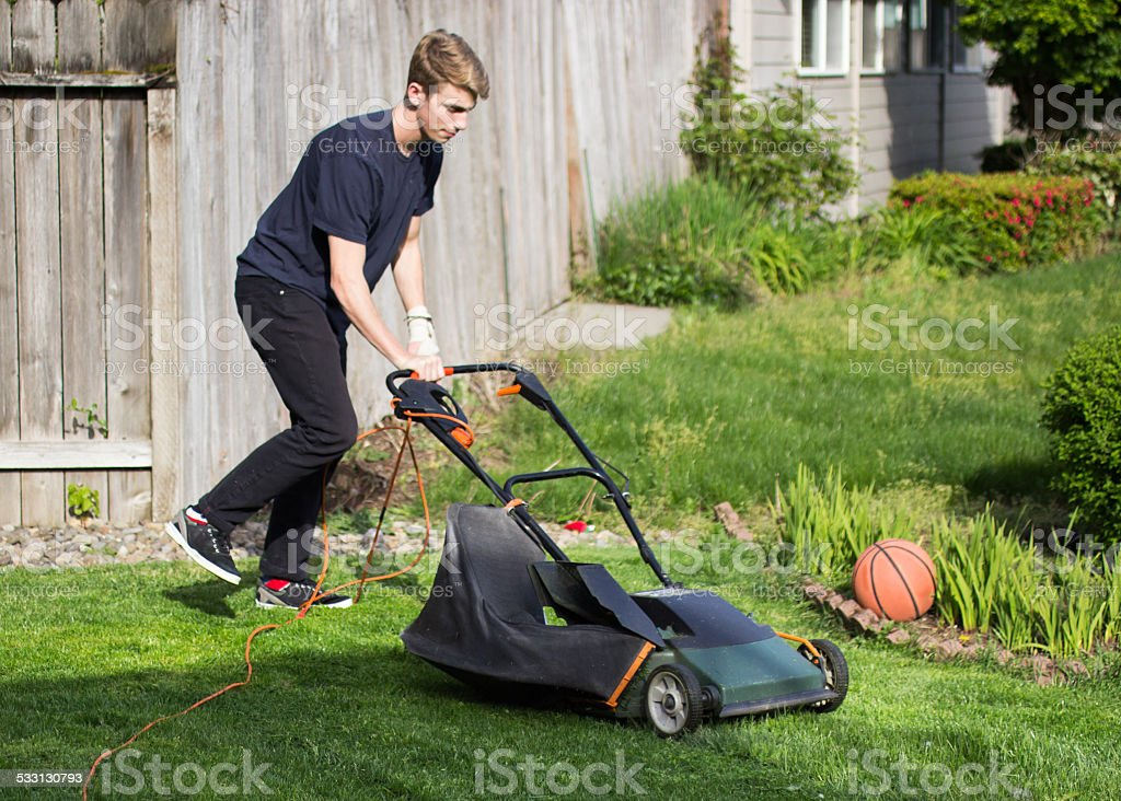 Young man mowing the lawn with an electric lawn mower stock photo
