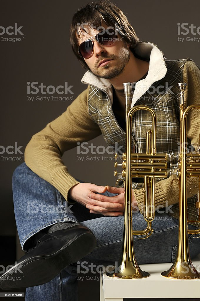 Young man, musician is sitting with his two golden trumpets stock photo