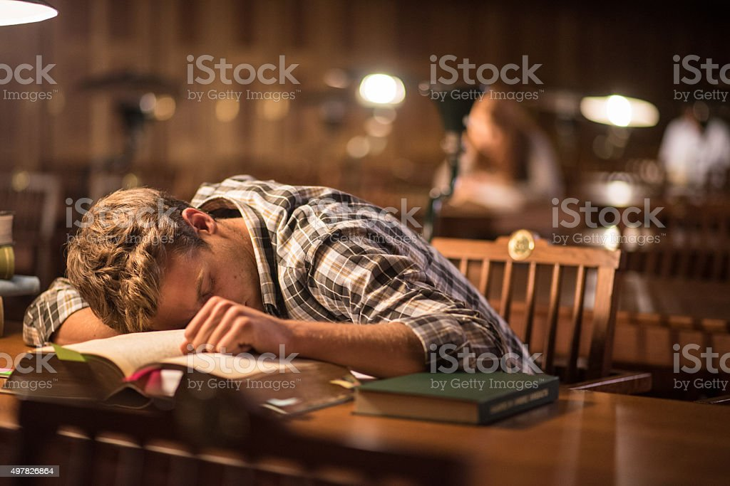 Young man napping in library stock photo