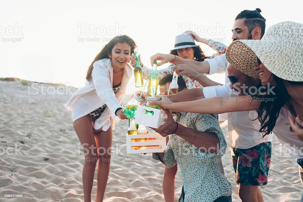 Young man offering drinks on the beach stock photo