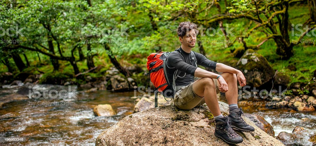 Young man on a hiking trip resting next to a river royalty-free stock photo