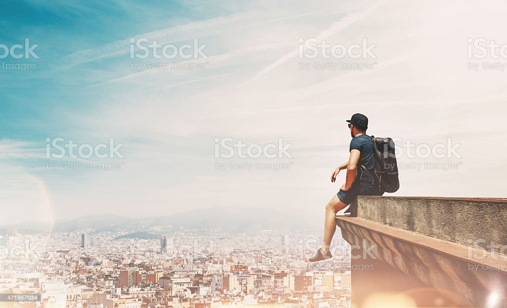 Young man on a roof looking at the city stock photo