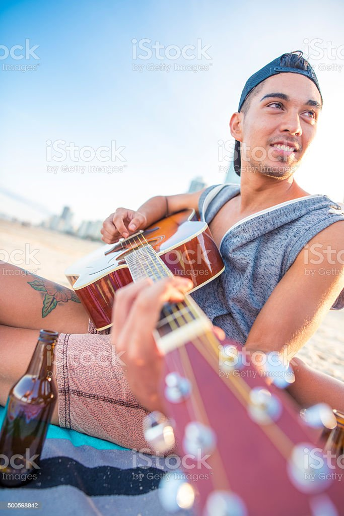Young man on beach playing guitar stock photo