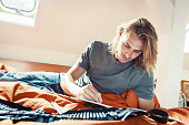 Young man on bed, drawing in coloring book