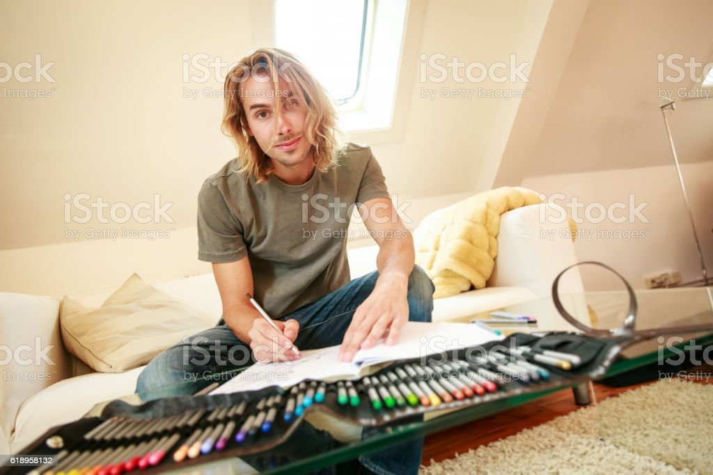 Young man on couch, drawing in coloring book stock photo