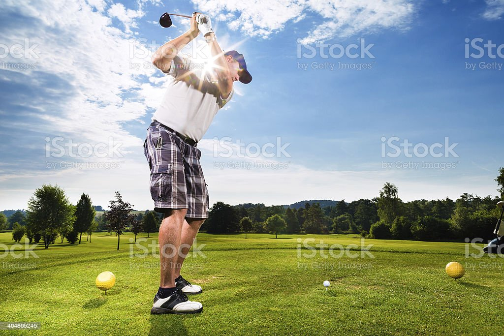 Young man on course doing golf swing stock photo