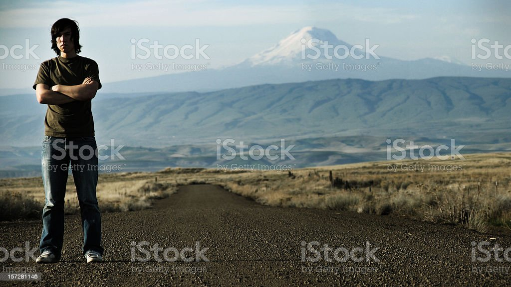 Young Man on Dirt Road with Mountain Landscape royalty-free stock photo