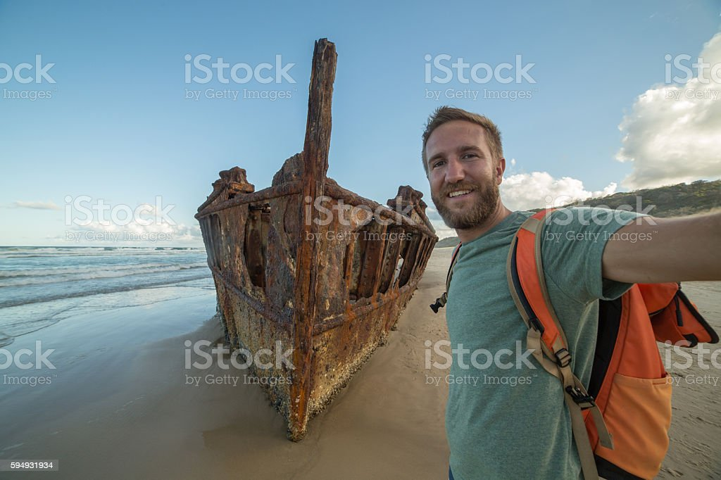 Young man on Fraser Island takes selfie portrait with shipwreck stock photo
