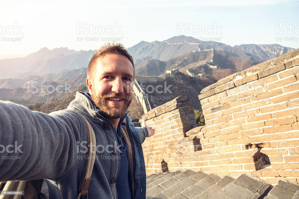 Young man on Great Wall of China taking selfie portrait stock photo