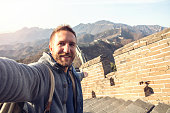 Young man on Great Wall of China taking selfie portrait